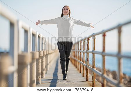 young woman with open arms walking