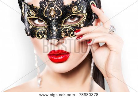 Beauty model woman wearing venetian masquerade carnival mask at party, over white background. Christmas and New Year celebration. Sexy girl with holiday makeup and manicure. Red lips and nails