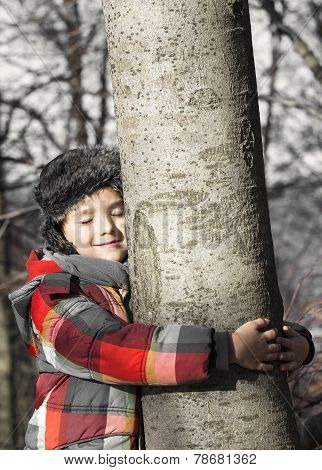 Boy Hugging A Tree, Listening The Sounds Of The Nature. Taking Care Of The Forest.