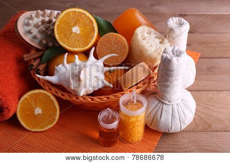 Spa accessories in wicker basket with rolled towel and compress balls on color bamboo mat on wooden background