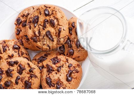 Chocolate cookies and milk in jug on white wood background