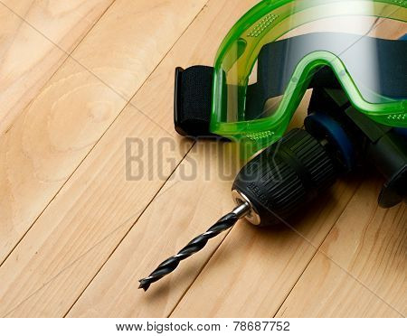 Handdrill And Goggles On Wooden Background
