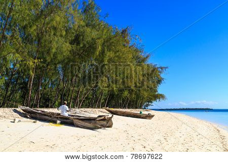 Fisherman Repairing His Traditional Boat Lying Near On The Beach