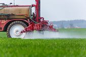 stock photo of pesticide  - Spraying machine working on the green field
