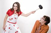 stock photo of adversity humor  - Young pretty wife strikes her husband in studio - JPG