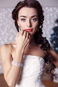 picture of studio  - fashion studio portrait of beautiful bride with long dark hair in elegant wedding dress with accessories posing in decorated studio with Christmas tree on background - JPG