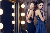 stock photo of studio  - fashion studio photo of two beautiful sensual women with dark hair in luxurious dresses with bijou - JPG