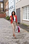 picture of girl walking away  - young woman walking with shopping bags and a take away coffee - JPG