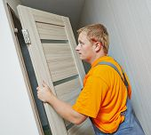 image of carpenter  - Male handyman carpenter at interior wood door installation - JPG