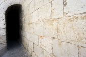 pic of dark side  - Side view of dark passage with antique stone wall - JPG