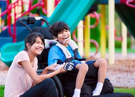 image of wheelchair  - Sister sitting next to disabled brother in wheelchair at playground - JPG