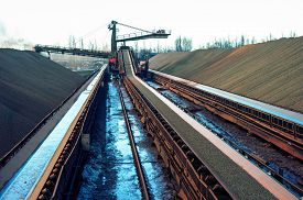 picture of iron ore  - loading iron ore conveyor machine from the warehouse mining production - JPG