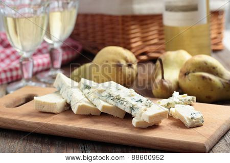 Sliced blue cheese, pears, and white wine on a rustic table
