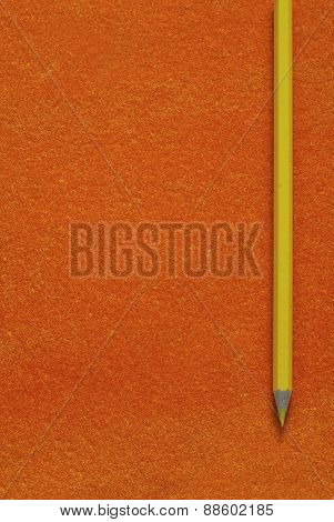 yellow pencil on orange texture background