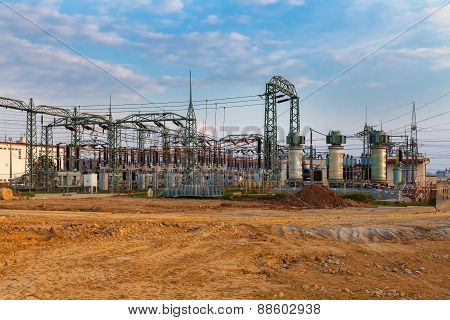 High voltage power transformer substation, field, blue sky