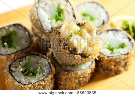 Japanese Cuisine - Deep-fried Sushi Roll with Scallop and Chuka Seaweed inside. Served on Wooden Plate