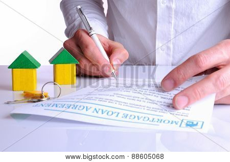 Client Signing The Mortgage Loan Agreement With Small Wooden Houses
