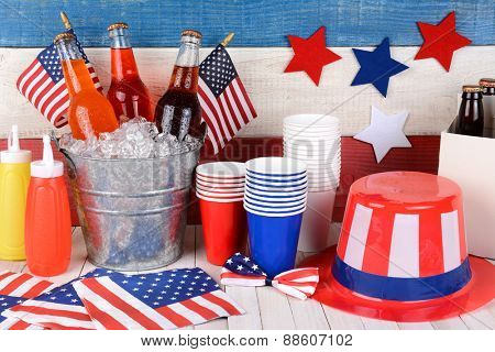 Fourth of July still life. A picnic table with a bucket of soda, flags, Uncle Sam hat, 6 pack, ketchup and mustard with a red, white and blue wall behind.