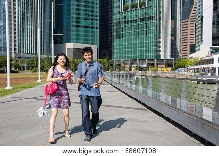 SINGAPORE - CIRCA FEBRUARY 2015: Happy young couple walking along the waterfront Marina Bay background CBD. Quay Marina Bay a popular place for walks among the tourists and locals.