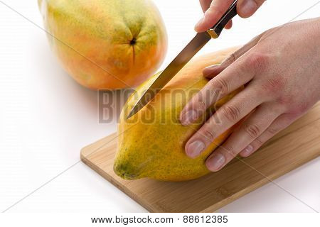 Knife Positioned For A First Cut Through A Papaya