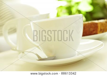 closeup of a white porcelain cup with coffee or tea, and a milk pot and a piece of cake in the background, on a coffee table