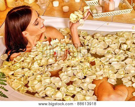 Woman relaxing at water spa. Black long hair .White rose petal.