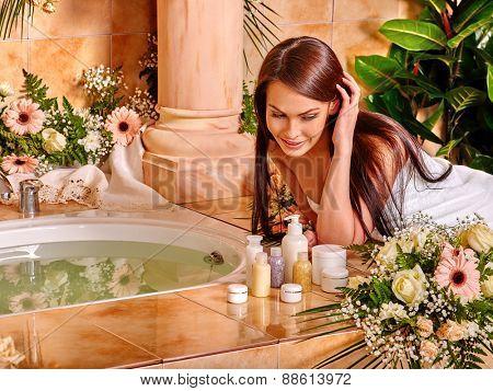 Woman relaxing at water spa. Girl looking at cosmetics.