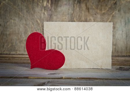The Form For A Card On Wooden Background .   Handmade Heart From Red Felt Is  In The Left Corner