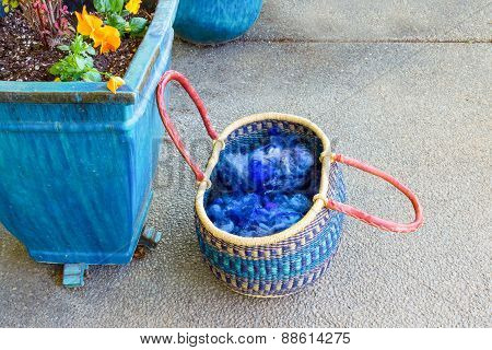Woven Basket With Wool And Yarn Next To A Planter