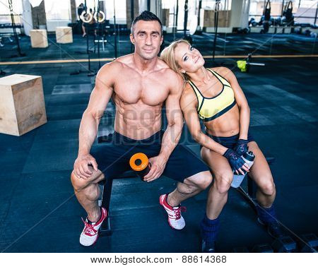 Handsome muscular man and beautiful sporty woman resting on bench at gym