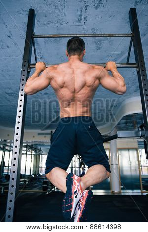 Back view portrait of a muscular handsome man pulling up at gym