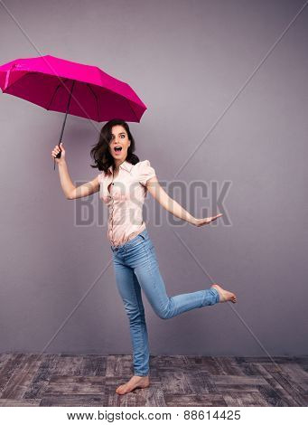 Full length portrait of a surprised woman posing with pink umbrella in studio. Wearing in jeans and shirt. Barefoot. Looking at camera