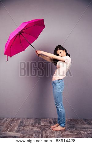 Full length portrait of a woman posing with pink umbrella over gray wall. Wearing in jeans and shirt. Barefoot. Looking at camera