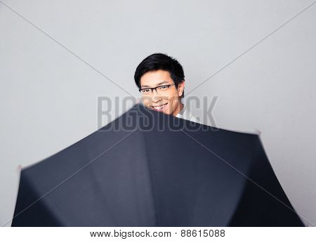 Portrait of a happy man in glasses with umbrella over gray background. Looking at camera