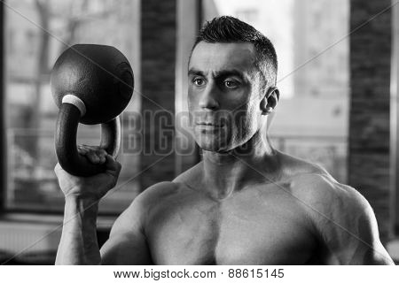 Black and white portrait of a bodybuilder holding kettle ball in gym