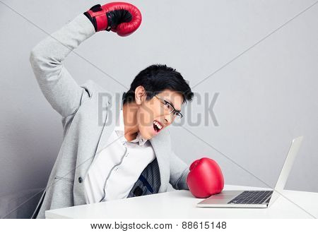 Angry young businessman sitting at the table in boxing gloves. Ready to hit the laptop