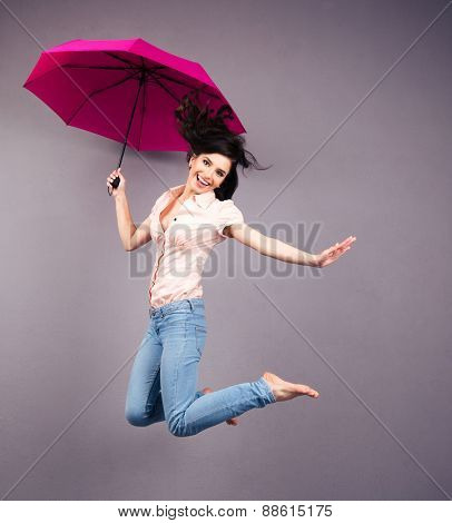 Happy young woman jumping with umbrella over gray background. Looking at camera