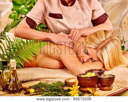 Blond woman getting massage in tropical spa. Fern in foreground