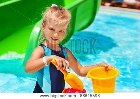 Child with bucket in swimming pool.  Summer outdoor. Yellow and blue.