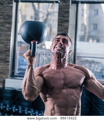 Bodybuilder man workout with kettle ball at gym