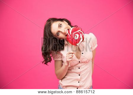 Young beautiful woman biting lollipop over pink background