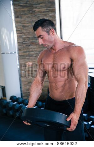 Handsome muscular man holding weight in gym