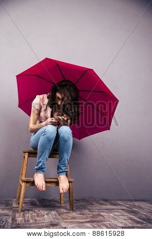 Woman sitting on the chair with pink umbrella and using smartphone at studio. Wearing in jeans and shirt. Barefoot