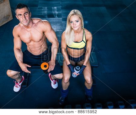 Muscular man and fit woman sitting on the bench at gym and looking at camera