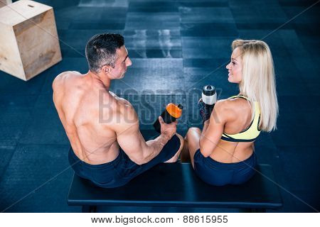 Back view portrait of a fit woman and muscular man sitting on the bench at gym