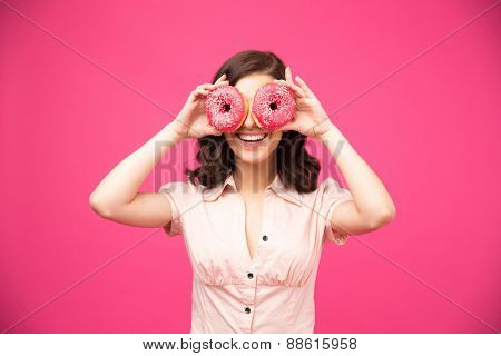 Woman covering her eyes with donut over pink donut