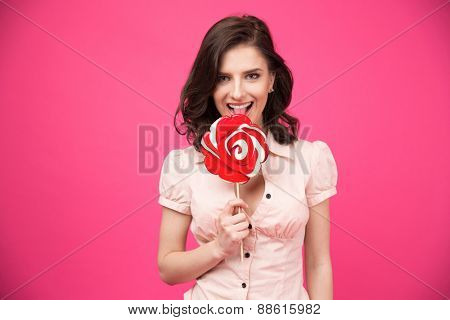 Happy woman holding lollipop with her tongue hanging out. Looking at camera