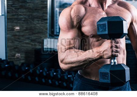 Closeup image of a muscular man workout with dumbbell