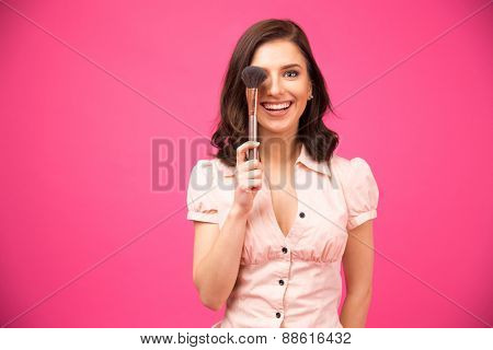 Happy young woman covering her eyes with brush for makeup. Looking at camera. Standing over pink background