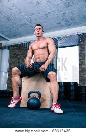 Muscular man sitting on fit box and reading for workout with kettle ball in gym. Looking at camera